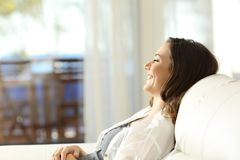 Woman relaxing on vacations in an apartment. Side view portrait of a happy woman relaxing on vacations sitting on a couch and looking through a window in an Royalty Free Stock Photo