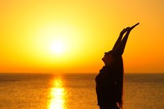 Happy woman profile raising arms at sunset on the beach royalty free stock images