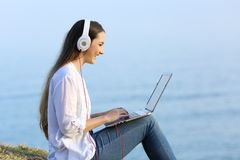 Woman watching and listening online content outdoors. Side view portrait of a happy woman watching and listening online content in a laptop outdoors on the beach Royalty Free Stock Photography