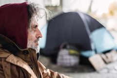 A side view portrait of homeless beggar man sitting outdoors. Copy space. royalty free stock photo