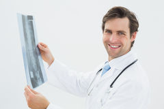 Side view portrait of a male doctor examining spine xray. Over white background Stock Images