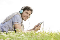 Side view portrait of man listening to music on MP3 player using headphones in park against clear sky Stock Images