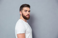 Side view portrait of a man looking at camera. Side view portrait of a man standing over gray background and looking at camera Stock Photography