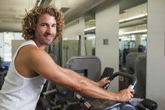 Side view portrait of man working out on exercise bike. Side view portrait of a young man working out on exercise bike at the gym Royalty Free Stock Images