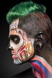 Side view portrait on man with zombie face art in bright colores. Scary zombie makeup for Halloween royalty free stock photography