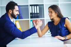 Side view portrait of man and woman armwrestling, exerting press royalty free stock image