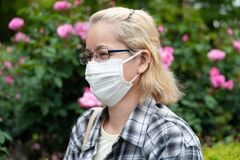 Side view portrait of middle aged mixed race blonde woman with eyeglasses wearing white surgical mask