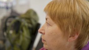 Side view portrait of old woman sitting at airport and waiting for trip.  stock footage