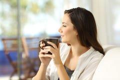 Pensive woman holding a coffee mug looking away Royalty Free Stock Photo