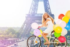 Girl cycling through Paris with balloons bouquet Stock Photography