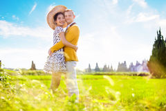 Side view portrait of romantic couple embracing on field Stock Images
