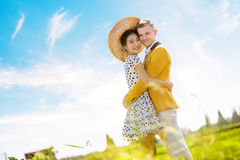 Side view portrait of romantic couple embracing on field against sky Royalty Free Stock Image