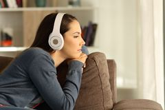 Pensive woman listening to music at home. Side view portrait of a sad pensive woman listening to music sitting on a couch in the living room at home Stock Image