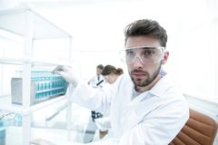 Young male scientist looking at a sample in a test tube side vie. Side view portrait of a scientist, uses a test tube and looking at the camera while working on Stock Photo