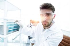 Young male scientist looking at a sample in a test tube side vie. Side view portrait of a scientist, uses a test tube and looking at the camera while working on Stock Images