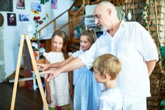 Mature Art Teacher Working with Children. Side view portrait of senior art teacher teaching group of children painting in art class explaining techniques and Royalty Free Stock Images
