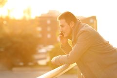 Man talking on phone in a balcony in winter. Side view portrait of a serious man talking on phone in a house balcony in winter at sunset stock photography