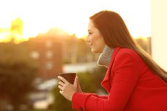 Serious pensive woman in winter in a balcony. Side view portrait of a serious pensive woman looking away in winter in a house balcony at sunset stock photos