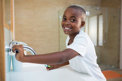 Side view portrait of smiling boy with toothbrush looking at mirror Stock Photography