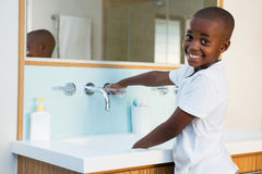 Side view portrait of smiling boy washing hands in sink Stock Image