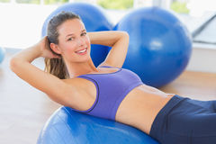 Side view portrait of a smiling fit woman lying on exercise ball Royalty Free Stock Image