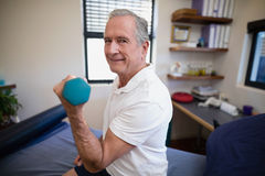 Side view portrait of smiling senior male patient lifting dumbbell. At hospital ward Royalty Free Stock Photography
