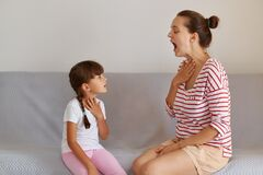 Side view portrait of speech pathologist demonstrating for little kid how to pronounce sounds right, Professional physiotherapist