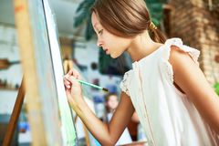 Talented Girl in Art Class. Side view portrait of talented pretty girl painting picture on easel in art class, with other children in background Royalty Free Stock Photos