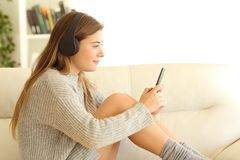 Profile of a teen listening to music at home. Side view portrait of a teen listening to music sitting on a sofa in the living room in a house interior in winter Royalty Free Stock Images