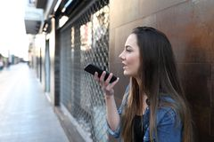 Teen using voice recognition on smart phone in the street stock photos