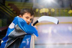 Young hockey player standing behind rink boards. Side-view portrait of teenage boy, professional ice hockey player, standing behind the rink boards stock image