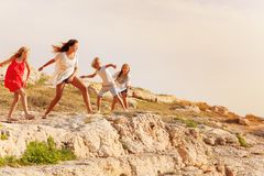 Joyful teens throwing stones on the cliff top royalty free stock photography