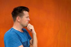 Side view portrait of thinking caucasian young man looking away. On red background. Concept of grumpy mood Stock Photo