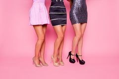 Side view portrait of three beautiful girls in dress showing their smooth legs on pink background royalty free stock photography