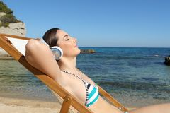 Tourist listening to music relaxing on the beach stock image