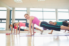 Side view portrait of trainer with class doing push ups Stock Photo