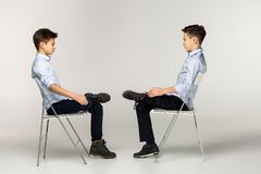 Side view portrait of two teenagers in blu shirts stock images