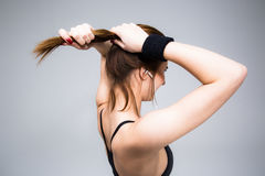 Side view portrait of a woman holding her hair. Over gray background Stock Photos