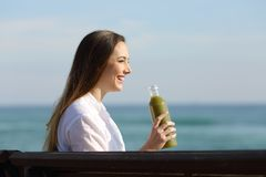 Side view of a woman holding a vegetable juice. Side view portrait of a woman holding a vegetable juice sitting on a bench on the beach royalty free stock images