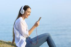 Woman listening to music relaxing on the beach Stock Images