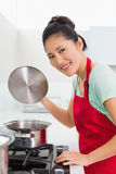 Side view portrait of a woman preparing food in kitchen Royalty Free Stock Photography