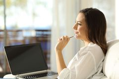 Woman thinking and showing a blank laptop screen Stock Photos