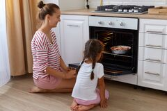 Side view portrait of woman wearing striped casual shirt and her daughter in white t shirt sitting on floor in kitchen and waiting