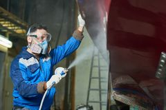 Worker Spray Painting Boats in Workshop Royalty Free Stock Images