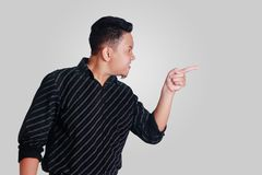 Young Asian Man Mad and Pointing. Side view portrait of young Asian man, angry mad boss pointing,  on grey Royalty Free Stock Image