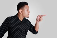 Young Asian Man Mad and Pointing. Side view portrait of young Asian man, angry mad boss pointing,  on grey Stock Photos