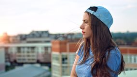 Side view portrait of young attractive teenage woman in cap enjoying beautiful sunset outdoor. On roof. Close up pretty female pensive traveler admireing view stock footage