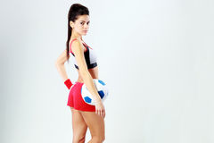 Side view portrait of a young beautiful woman standing with soccer ball Royalty Free Stock Image