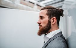 A side view portrait of young businessman in office. Copy space. stock images
