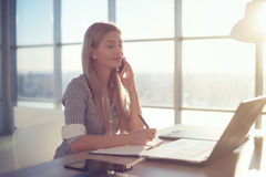 Side view portrait of young businesswoman having business call in office, her workplace, writing down some information. Woman talking on mobile phone, asking stock photography